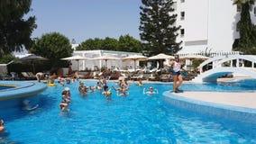 Hammamet, Tunísia - 25 de julho de 2017: Os turistas são contratados na ginástica aeróbica do aqua no clube Novostar Sol Azur Bea filme