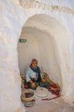 HAMMAMET, TUNESIË - Oct 2014: De vrouw maalt korrel in berberhuis op 7 Oktober, 2014 Royalty-vrije Stock Afbeeldingen