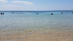 Hammamet, Tunisia - 25 luglio 2017: I turisti stanno bagnando nel mare e stanno rilassando sulla spiaggia video d archivio