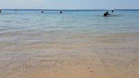 Hammamet, Tunisia - 25 luglio 2017: I turisti stanno bagnando nel mare e stanno rilassando sulla spiaggia stock footage