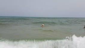 Hammamet, Tunisia - 25 luglio 2017: La ragazza non identificata è stata coperta da un'onda del mare nel mare stock footage