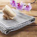 Hamman or sauna brush and towel on wood background for exfoliation. Back brush for beauty ritual at spa center with towel and flowers for femininity Stock Photography