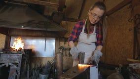 Hammare för kvinnahovslagareslag på den varma metallworkpiecen stock video