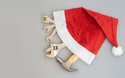 Hammare justerbar skiftnyckel, skiftnycklar i Santa Hat Behändiga hjälpmedel i begrepp för julfestivalbakgrund arkivfoton