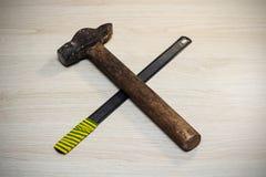 Hammare- och sågcloseup på en trätabell arkivfoto