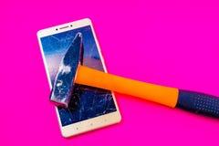 Hammare som slår den smarta telefonen på en magentafärgad bakgrund royaltyfria bilder