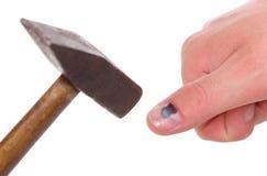 Hammaren och fingret med mörbultad svart spikar på vit bakgrund Arkivbild