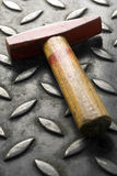 Hammer. A red head hammer on a metal surface (shallow depth of field Royalty Free Stock Photo