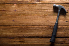 Hammer. A hammer with a black grip, on a wooden surface