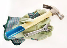 Hammer with an adjustable wrench lie on protective gloves Stock Photography