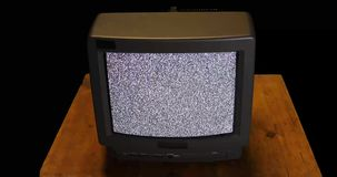Hammer aimed at retro TV screen with snow and noise stock footage