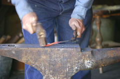 Hammer and Anvil. A blacksmith?s hammer forges red hot steel on an anvil Royalty Free Stock Image