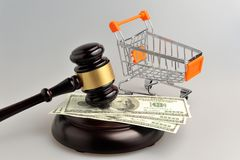 Hammer of auctioneer with pushcart and money on gray Stock Photos