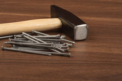 Hammer with big pile of nails on table. Hammer with big pile of nails on brown wood table, front view Royalty Free Stock Photo