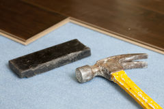 Hammer and Block with New Laminate Flooring Stock Photo