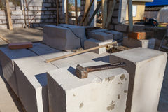 The hammer on the bricks of foam concrete. Stock Images