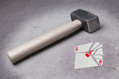 Hammer with a broken card, ace of hearts Stock Image