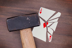 Hammer with a broken card, ace of hearts Royalty Free Stock Photos