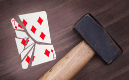 Hammer with a broken card, seven of diamonds Royalty Free Stock Photo