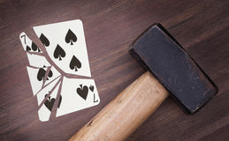 Hammer with a broken card, seven of spades Royalty Free Stock Photography