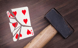Hammer with a broken card, six of hearts Stock Photo
