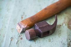 Hammer with a broken handle on a wooden background royalty free stock image