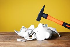 Hammer and broken piggy bank with money on  table against color background Stock Photography