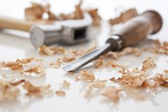 Hammer and chisel. On a white board with sawdust shavings Stock Image