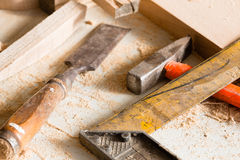 Hammer, chisel and angle carpenter lie on a workbench Royalty Free Stock Image