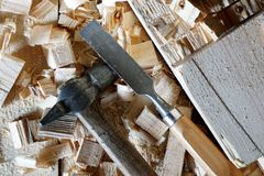 Hammer and chisel lie on the boards. Hammer and chisel are on the boards among the chips royalty free stock images