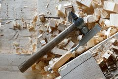 Hammer and chisel lie on the boards. Hammer and chisel are on the boards among the chips royalty free stock image