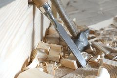 Hammer and chisel lie on the boards. Hammer and chisel are on the boards among the chips stock photo