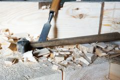 Hammer and chisel lie on the boards. Hammer and chisel are on the boards among the chips stock image