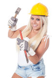 Hammer and chisel. Young blonde girl working as building labor with a yellow helmet, hammer and chisel or gouge stock photo