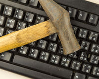 Hammer on damaged computer keyboard Stock Photo