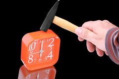 Hammer destroys the alarm clock. The hand holds the hammer over the alarm clock Stock Image