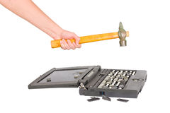 Hammer destroys laptop. Hand with a hammer destroys laptop Stock Image