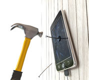 hammer and digital tablet on wooden desk with nails concept Royalty Free Stock Photo