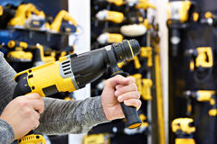 Hammer drill in hands at shop. Hammer drill in man`s hands closeup Royalty Free Stock Photo