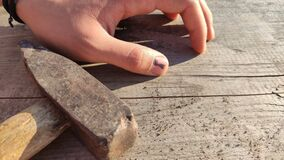 A hammer and a finger with a black bruised nail against the background of an old wooden table. very painfully.