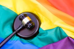 Hammer and gavel again against rainbow flag. Hammer and gavel against against rainbow flag. gay flag background stock image