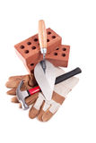 Hammer, Glove, Brick and trowel. On isolated white Royalty Free Stock Images