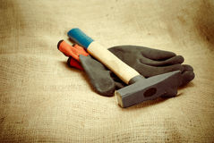 Hammer and gloves. On the table Stock Photos