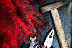 Hammer, gloves and wrenches. On a dark background Royalty Free Stock Image