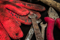 Hammer, gloves and wrenches. On a dark background Stock Photography