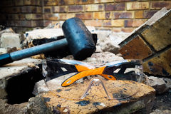 Hammer and Goggles. Construction demolish and break down brick wall brown and concrete. Broken Pieces. Chunks of Bricks. Crumble down. Construction Build Royalty Free Stock Images
