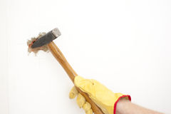 Hammer smashing hole in white house wall. Hammer in hand with gloves of man smashing hole in white home brick wall, demolishing, damaging house room, isolated Stock Photography