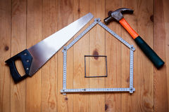 Hammer, hand saw, meter, nails are in  form of  house. House concept. Stock Image