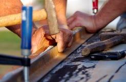 Hammer in hand. Two men bending sheet metal Royalty Free Stock Photos