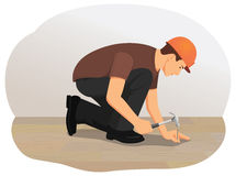 Hammer. Handyman hammering a nail into wood. Installing wooden flooring Royalty Free Stock Image
